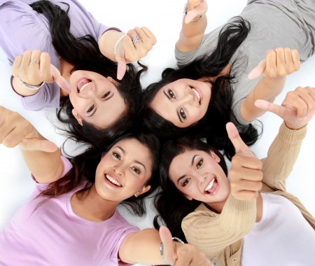 Photo for four young attractive asian women relaxing smiling lying on the floor showing thumbs up - Royalty Free Image