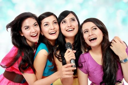 Four beautiful young woman singing karaoke together
