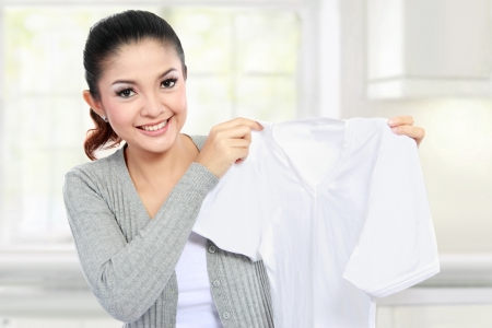 young smiling asian woman showing white clean clothes