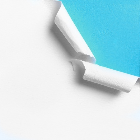 Piece of white paper with torn hole edge over blue background