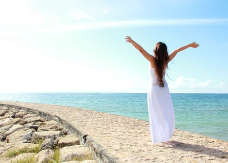 Woman relaxing at the beach with arms open enjoying her freedom wear long white dress