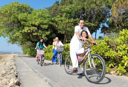 Foto de Happy asian family riding bikes in the beautiful morning at the beach. Outdoor portrait - Imagen libre de derechos