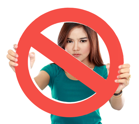 Close up of young woman holding prohibited sign