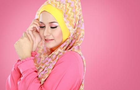 Fashion portrait of young beautiful muslim woman with pink costume wearing hijab