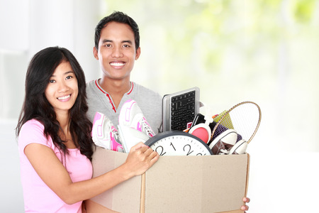 man and woman with their stuff inside the cardboard box ready to move  moving day concept