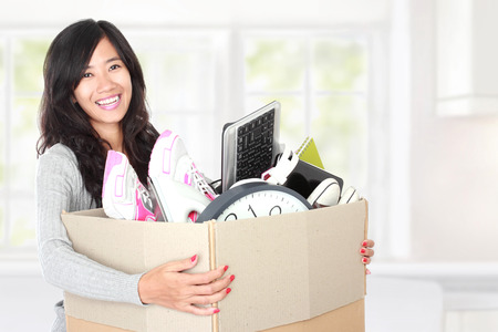 woman with her stuff inside the cardboard box ready to move. moving day concept