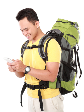 portrait of a smiling male hiker with backpack using mobile phone isolated on white background