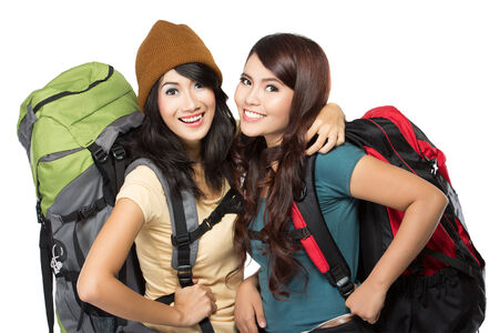portrait of two happy young girl bring backpack and hug each other