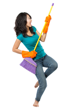 Cleaning girl happy excited during cleaning. Funny girl with cleaning mop playing guitar isolated on white background