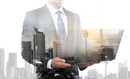 Double exposure of city and businessman using laptop computer