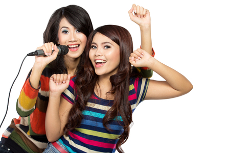 A portrait of two asian girls in striped t-shirt singing together