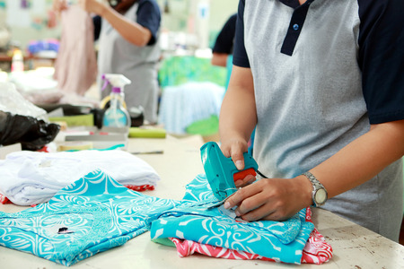 Photo pour portrait of labelling process for cloting product at textile factory - image libre de droit