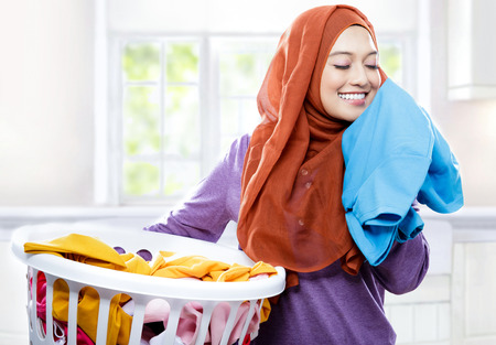 portait of young woman wearing hijab carrying laundry basket while smelling fresh clean clothes