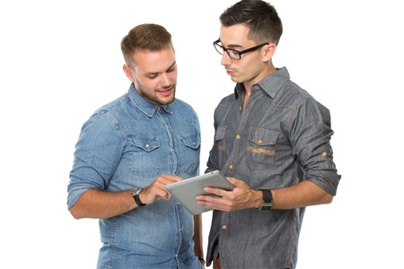 Photo pour portrait of two young  man discussing over a tablet pc, isolated over white background - image libre de droit