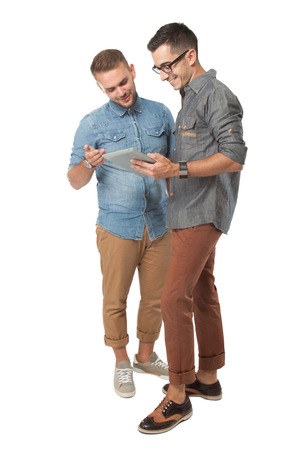 Photo pour portrait of two young  man looking at a tablet pc, isolated over white background - image libre de droit
