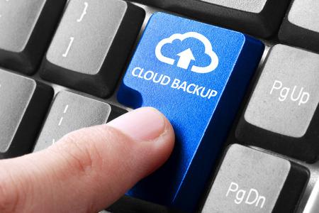 Photo pour Back up online via cloud. gesture of finger pressing cloud backup button on a computer keyboard - image libre de droit