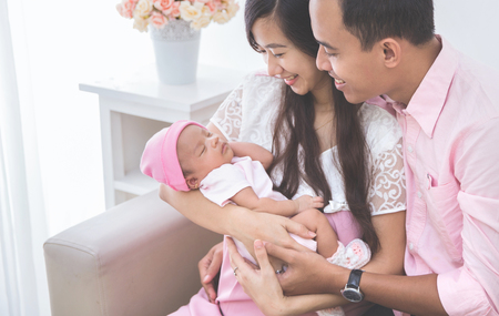 Photo pour Couple looking at their sleeping baby girl, close up - image libre de droit