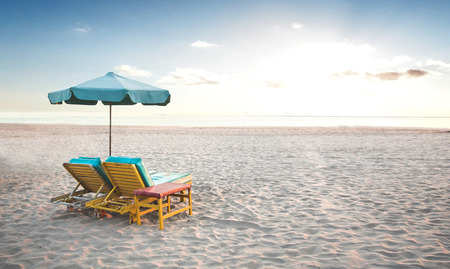 Photo pour A portrait of a pair of beach chair with umbrella in a seashore - image libre de droit