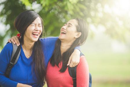 Foto de A portrait of happy two young Asian students laugh, joking around together - Imagen libre de derechos