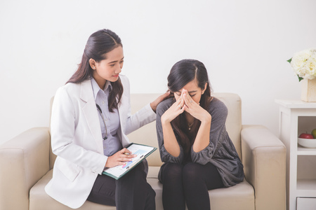 Photo pour A portrait of Asian female patient crying while consulting her health problem with a female doctor - image libre de droit