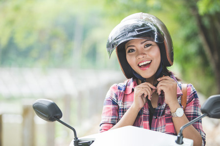 Photo for A portrait of a young asian woman wearing a helmet before riding a motorcycle on a park - Royalty Free Image