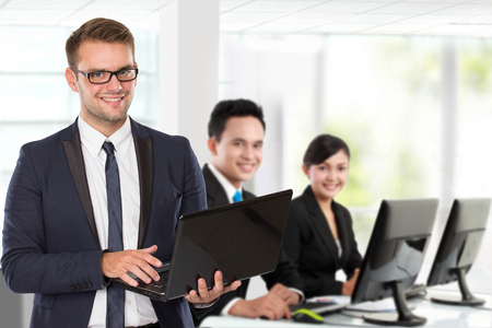 Photo pour A portrait of a young caucasian businessman, with his team behind holding laptop. isolated in white background - image libre de droit