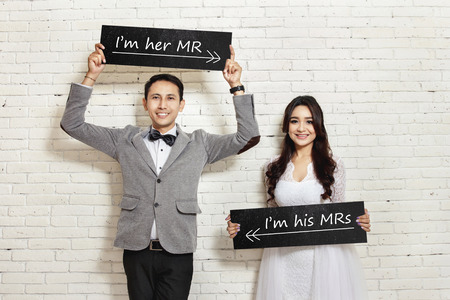 Foto de portrait of handsome groom and beautiful bride smiling while holding board with white wall background - Imagen libre de derechos