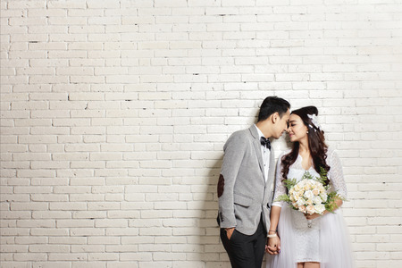 Photo for portrait of lovely asian newlywed couple with copy space on white wall background - Royalty Free Image