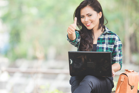 Photo for A portrait of a young asian woman using laptop while sitting on the park and showing thumb up - Royalty Free Image