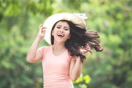 Photo pour A portrait of a beautiful young asian woman wearing round hat on a park - image libre de droit