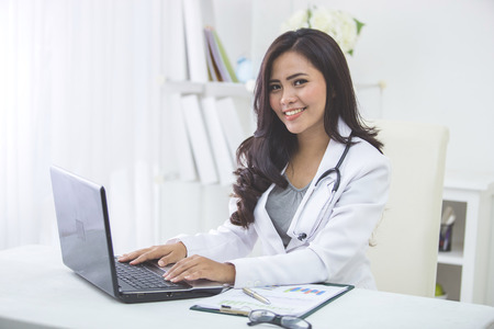Photo pour smiling asian female doctor working in office - image libre de droit