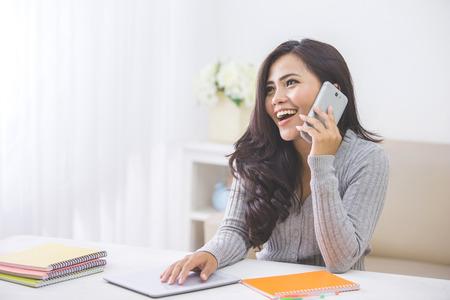 Photo pour portrait of casual asian woman making a phone call at home using smart phone - image libre de droit