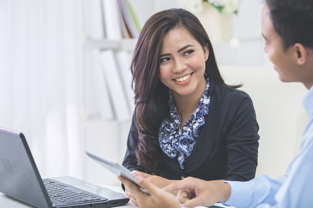 Foto per Image of two young asian business people at the meeting in the office - Immagine Royalty Free