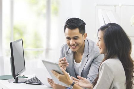 Foto de portrait of two business people talk about business at the office and using tablet pc - Imagen libre de derechos