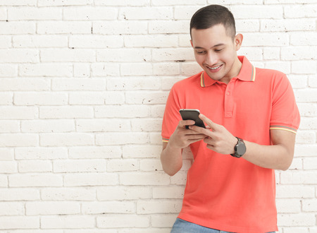 Photo pour portrait of handsome man texting on mobilephone with copy space on white brick wall background - image libre de droit