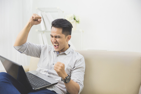 Photo for happy excited young man with laptop at home sitting on a couch - Royalty Free Image