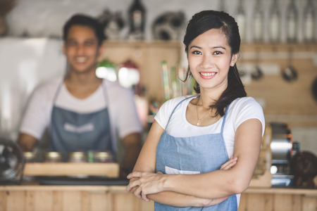 Foto de Successful small business owner standing with crossed arms with partner at the background - Imagen libre de derechos