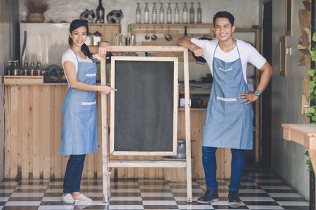 Photo pour happy two small business owner ready to open their cafe. standing with blank board - image libre de droit