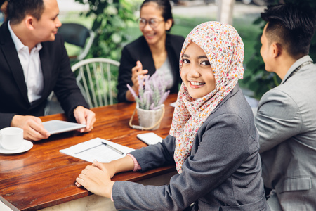 Photo pour Attractive asian businesswoman smiling at the camera during a business meeting - image libre de droit
