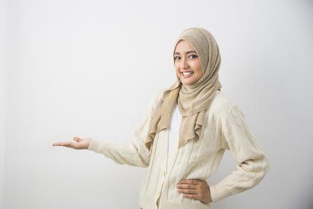 Photo pour Portrait of a young muslim woman showing blank area for sign or copyspace - image libre de droit