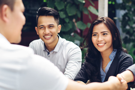 Photo for portrait of young asian business people meeting in a cafe and shake hand - Royalty Free Image