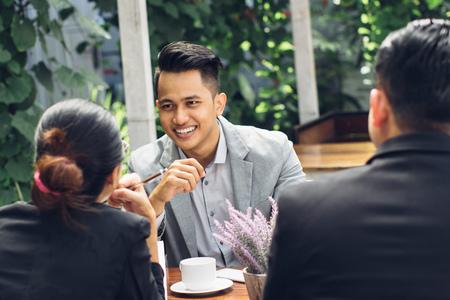 Photo pour candid portrait of a confident businessman meeting at cafe with his team - image libre de droit