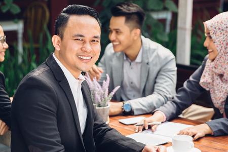 Photo pour handsome businessman smiling at the camera during a business meeting - image libre de droit