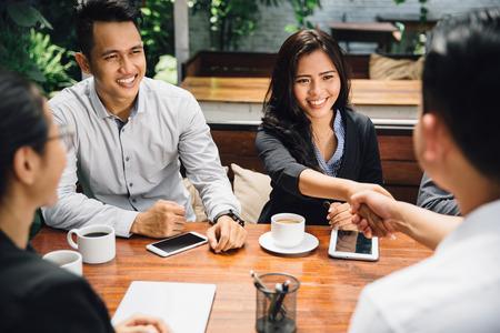 Photo pour portrait of Business people shaking hands, finishing up a meeting - image libre de droit