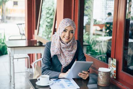 Photo pour Young businesswoman on a coffee break. Using tablet computer - image libre de droit
