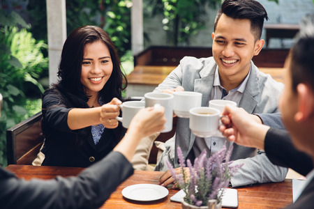 Photo for happy asian business Friends Cheering With Coffee at cafe - Royalty Free Image