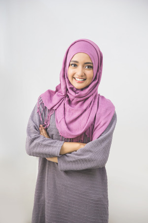 Photo pour Young asian muslim woman in head scarf smile with arms crossed - image libre de droit