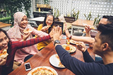 Photo pour portrait of asian friend giving high five at cafe while having a lunch - image libre de droit