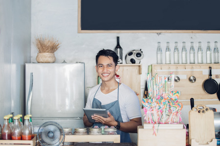 Photo for portrait of small business owner at his coffee shop using tablet pc - Royalty Free Image