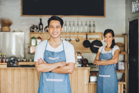 Photo pour Successful small business owner standing with crossed arms with partner at the background - image libre de droit